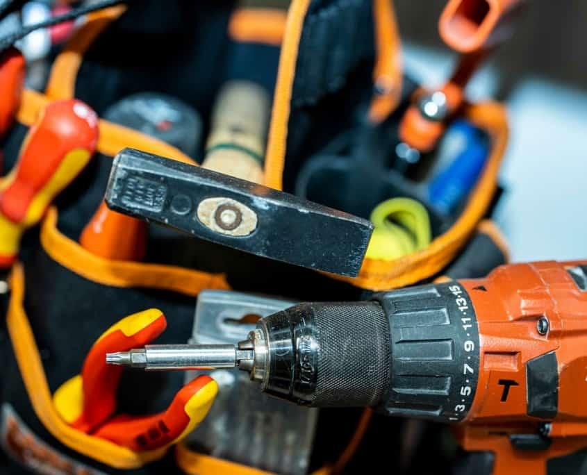Nærbillede af skruemaskine, hammer og værktøjsbælte